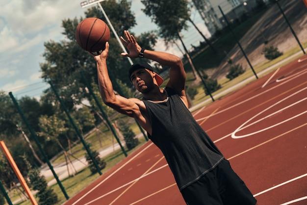 エネルギーに満ちています。屋外でバスケットボールをしながらボールを投げるスポーツウェアの若いアフリカ人