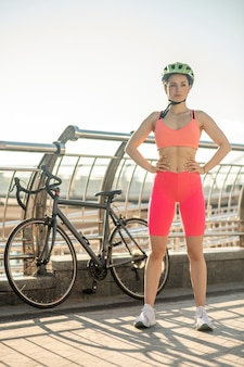 エネルギーに満ちています。橋に立って決意を持って見ている明るいスポーツウェアの若いサイクリスト