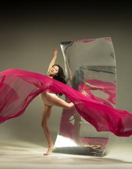気持ちいっぱい。鏡付きの茶色の壁にモダンなバレエダンサー。表面での錯覚の反射。柔軟性の魔法、生地による動き。クリエイティブアートダンス、アクション、インスピレーションのコンセプト。