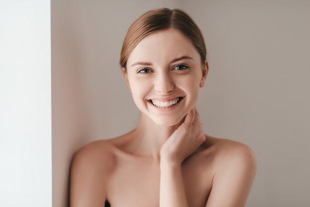 Полный жизненной энергии. привлекательная молодая женщина с веснушками на лице смотрит в камеру и держит руку на шее