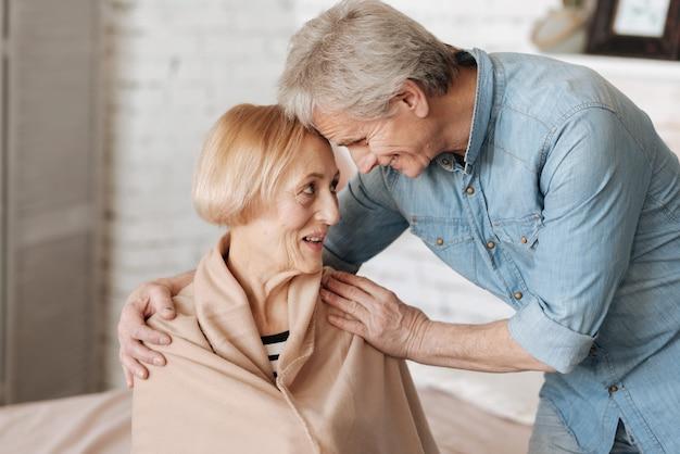 사랑이 가득합니다. 남자가 숙녀의 호의를 채우고 그녀에게 담요를 담그는 동안 함께 웃고 사랑스러운 매력적인 노인