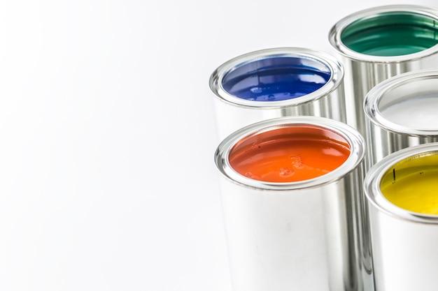 Полный разноцветных банок с краской на белом столе.