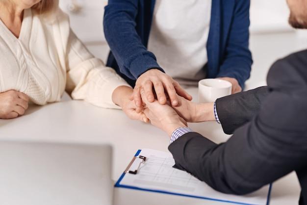 信頼に満ちています。家に座って握手しながら不動産業者と契約を結ぶポジティブな老夫婦を巻き込んだ