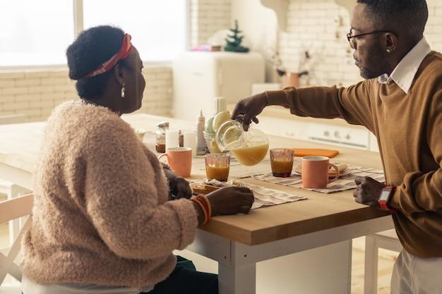 비타민이 가득합니다. 그의 아내를 돌보는 동안 오렌지 주스를 붓는 좋은 잘 생긴 남자