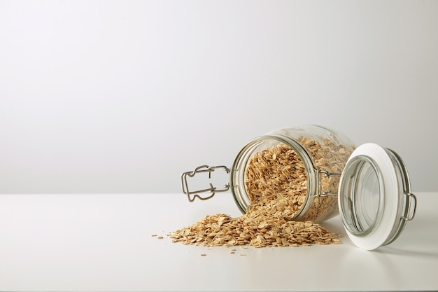 Full opened rustic jar with healthy rolled oats spread out isolated in center on white table side view