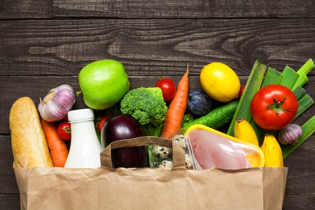 Full paper bag of different health food on rustic wooden background