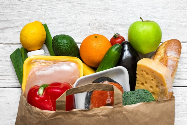 Full paper bag of different healthy food on white wooden background. fruits, vegetables, fish and chicken meat