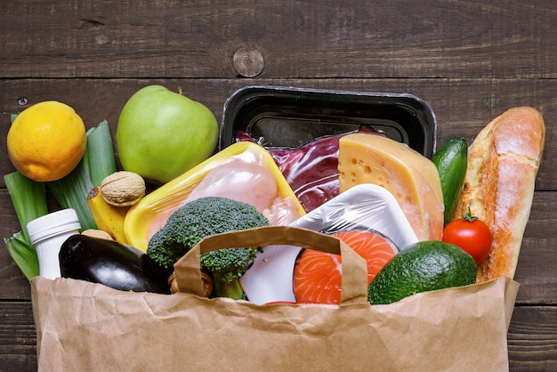 Full paper bag of different healthy food on white wooden table. fruits, vegetables, fish and meat
