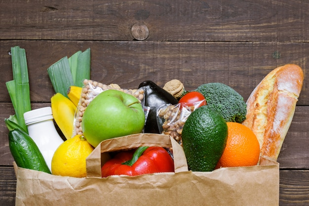 Full paper bag of different healthy vegetarian food on rustic wooden table. top view