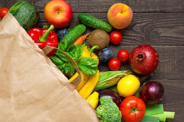 素朴な木製の背景にさまざまな果物と野菜の完全紙袋