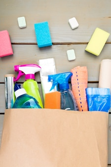 Полный бумажный пакет с различными продуктами для уборки дома,