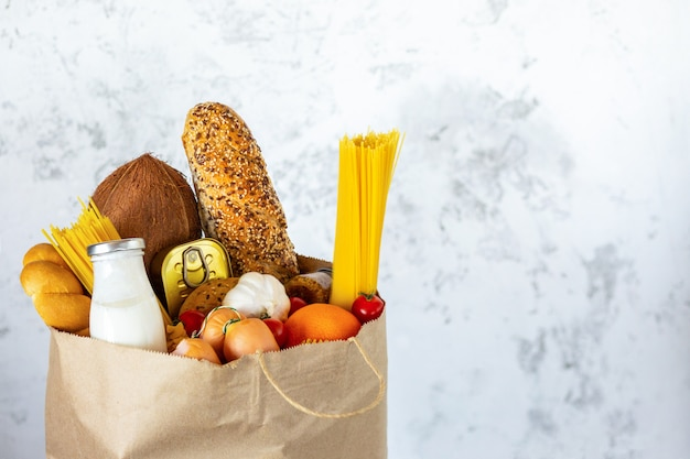 Полный бумажный мешок со здоровой пищей. здоровая пища фон. концепция продовольственного супермаркета. молоко, сыр, хлеб, фрукты, овощи, авокадо, ананас и спагетти. покупки в супермаркете. доставка на дом