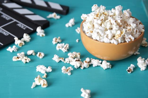 Полная тарелка попкорна, концепция фильма, крупный план попкорна в миске с соленым попкорном на старом деревянном столе.