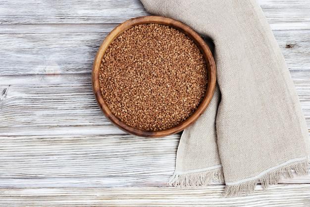 Полная тарелка с гречкой на деревянных фоне деревенский стиль.