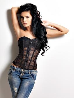 Ritratto completo della giovane e bella donna sexy con lunghi capelli neri in posa vestita di jeans e corsetto