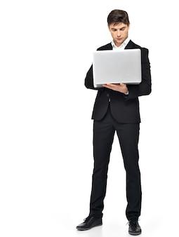 Ritratto completo dell'uomo d'affari che lavora al computer portatile isolato su bianco.
