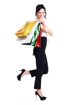 Full portrait of happy woman with color shopping bags standing isolated on white background.