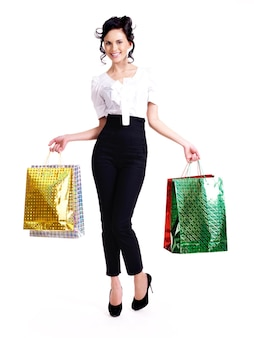 Ritratto completo di donna felice con i sacchetti della spesa di colore in piedi isolato sul muro bianco.