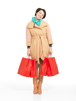 Ritratto completo di donna felice con borse della spesa in cappotto di autunno con sciarpa verde in piedi isolato su bianco