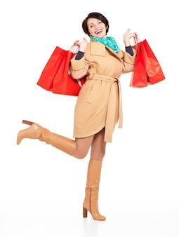 Full portrait of happy woman with shopping bags in autumn coat with green scarf standing isolated on white