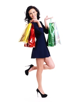 Full portrait of happy woman with shopping bags in blue dress standing isolated on white background.