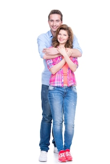 Full portrait of happy young couple isolated on white wall.