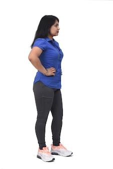 白い背景、側面図、腰に手でラテン女性の完全な肖像画