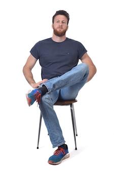 Полный портрет человека, сидящего на ножках стула, скрещенных над белой стеной