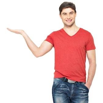 笑顔の男の完全な肖像画は、白い壁に隔離された手のひらに何かを保持しています。