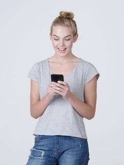 웃는 여자의 전체 초상화는 스튜디오에서 휴대 전화에 문자 메시지를 입력합니다