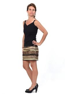真面目で腰に手を当てて、スカートをはいた女性の完全な肖像画