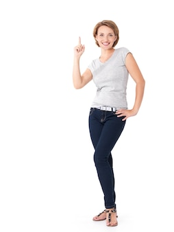 Полный портрет взрослой счастливой женщины, указывая пальцем на белом