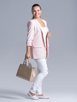 Полный портрет молодой счастливой женщины с сумочкой, позирующей в студии