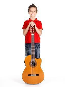 Полный портрет кавказского мальчика с акустической гитарой -