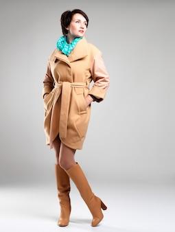 Полный портрет модницы в бежевом осеннем пальто с зеленым шарфом на сером фоне