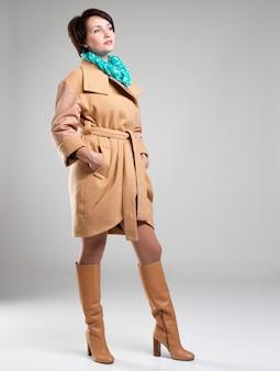 회색 배경에 녹색 스카프와 베이지 색 가을 코트에 패션 여자의 전체 초상화