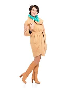 ベージュの秋のコートと白で隔離の緑のスカーフが立っている革のブーツで幸せな女性の完全な肖像画