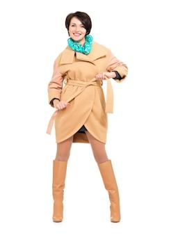 Полный портрет счастливой женщины в бежевом осеннем пальто и кожаных сапогах с зеленым шарфом, стоящим изолированным на белом