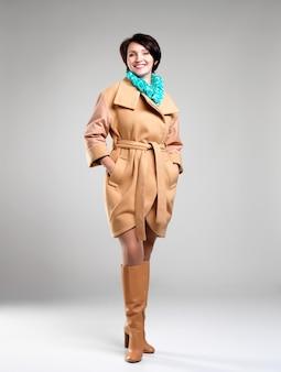 Полный портрет счастливой женщины в бежевом осеннем пальто с зеленым шарфом на сером фоне