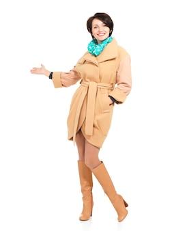Полный портрет счастливой женщины в бежевом пальто с зеленым шарфом, указывающей на что-то - стоя изолированным на белом