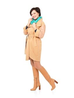 白で隔離の緑のスカーフ立っている秋のコートの革のブーツで幸せな女性の完全な肖像画