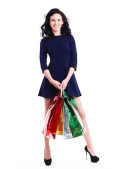 白い背景で隔離の青いドレス立っている買い物袋と幸せな女性の完全な肖像画。