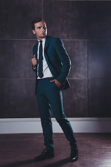 黒のスーツで豊かなスタイリッシュなハンサムな男の完全な肖像画