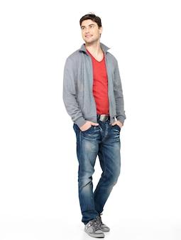 灰色のジャケット、ブルージーンズで笑顔の幸せなハンサムな男の完全な肖像画。離れて白を探して孤立して立っている美しい男