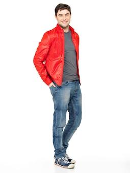 Полный портрет улыбающегося счастливого красивого человека в красной куртке, синих джинсах и тренажерных залах. красивый парень, стоящий на белом фоне