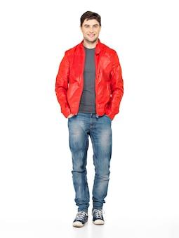 赤いジャケット、ブルージーンズ、ジムシューズで笑顔の幸せなハンサムな男の完全な肖像画。白で隔離立っている美しい男