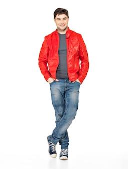 Полный портрет улыбающегося счастливого красивого человека в красной куртке, синих джинсах и тренажерных залах. красивый парень, стоящий на белом