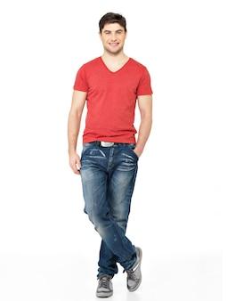 白い背景で隔離の赤いtシャツカジュアルで笑顔の幸せなハンサムな男の完全な肖像画。ポーズの美しい若い男