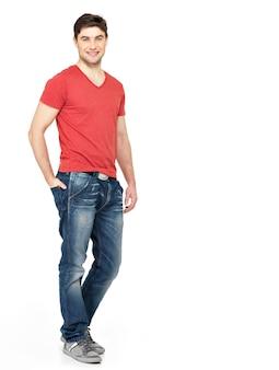 白い壁に分離された赤いtシャツカジュアルで笑顔の幸せなハンサムな男の完全な肖像画。ポーズをとる美しい若い男