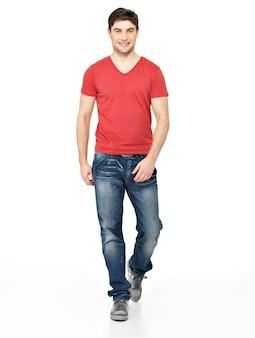 흰색 배경에 고립 된 빨간 티셔츠 캐주얼에 웃는 걷는 남자의 전체 초상화.